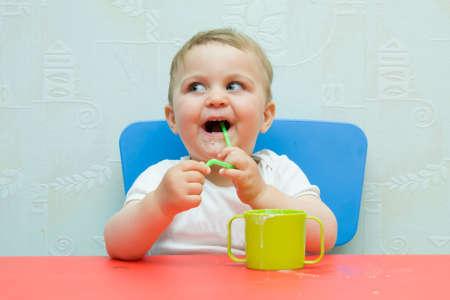 little, cute baby boy drinking milk with a straw photo
