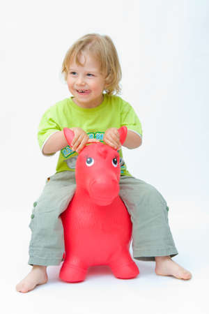little happy boy playing with red jumping animal photo