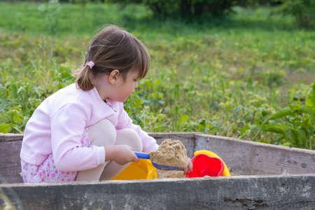 the sandbox: cute, little girl playing in the sandbox
