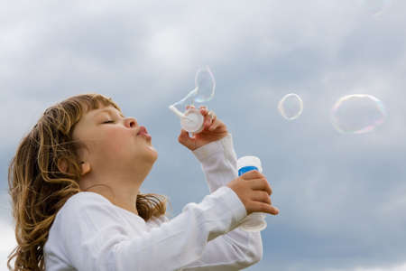 girl blowing: cute, little girl blowing soap bubbles against blue sky