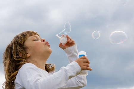 niedliche, kleine Mädchen bläst Seifenblasen gegen den blauen Himmel