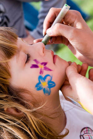 little, cute girl having her cheeks painted