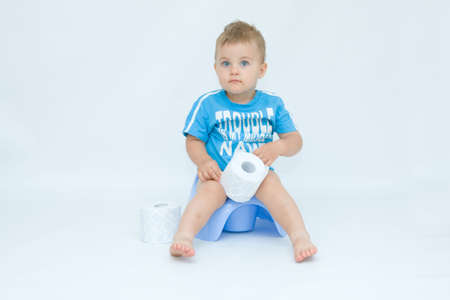 cute, little boy while potty training, on white