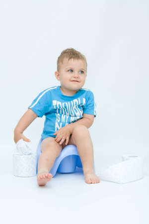 cute, little boy while potty training, on white photo