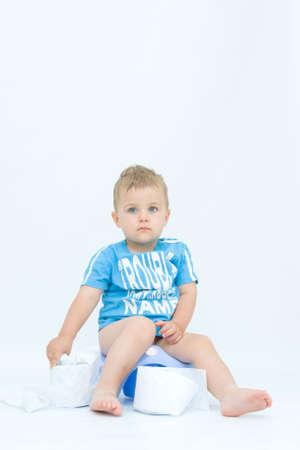 potty training: cute, little boy while potty training, on white