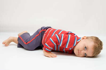 innocense: cute, little boy lying on white background