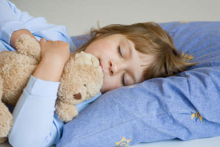 cute little girl sleeping on a blue pillow Stock Photo