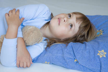 cute little girl sleeping on a blue pillow photo