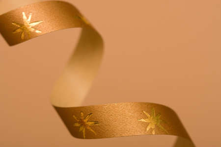 golden holiday background decorated with spiral ribbon photo