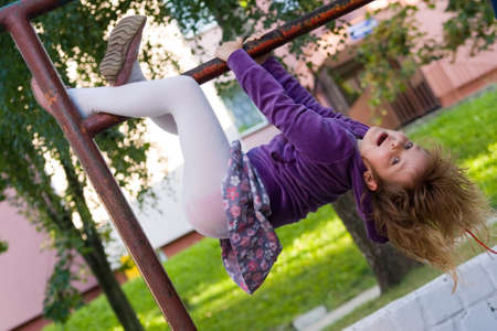 upside down: cute, little pretty girl having fun outdoors