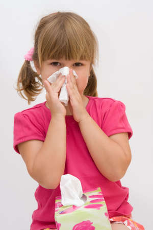 bad hygiene: cute, little girl blowing out her nose, on white