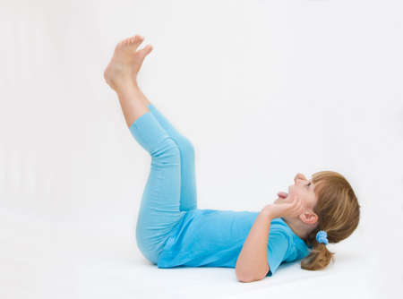 sport clothes: little girl in blue sport clothes exercising, on white