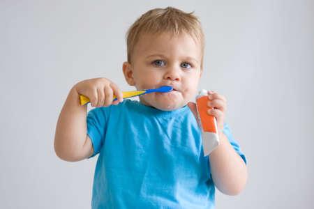 cute, little boy brushing his teeth photo