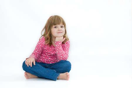 crosslegged: cute little girl sitting cross-legged, on white