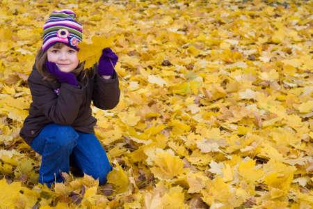 young leaf: lindo. ni�a jugando con hojas ca�dos