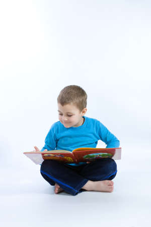 cute, little boy reading a book on white photo