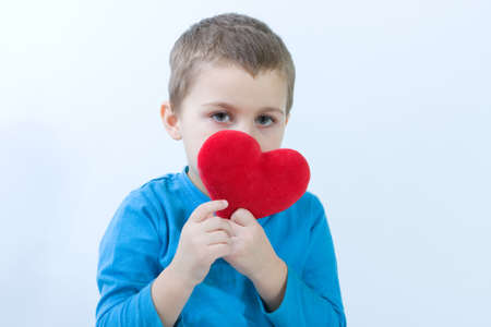 cute, little boy with heart on white background photo