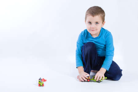 cute, little boy playing with toys on white photo