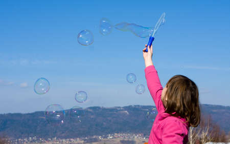 little girl making soap bubbles on a spring day photo