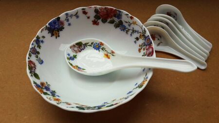 crockery bowl and spoon isolated on brown background closeup image