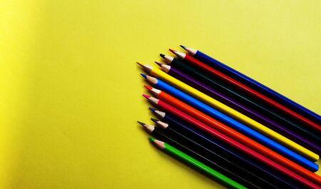 Lápices de colores aislados sobre fondo amarillo con espacio de texto Foto de archivo