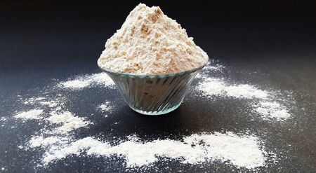 wheat flour in bowl isolated on black background Stock Photo