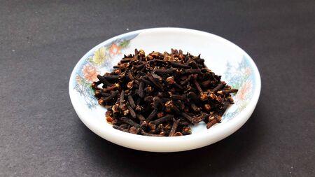 indische Gewürznelken in Schüssel auf schwarzem Hintergrund isoliert