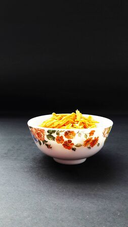 potato sticks indian snacks in bowl isolated on black background