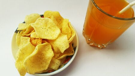 rice onion chips in bowl isolated on white background with glass of juice