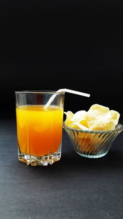 orange juice glass with rice onion chips isolated on black background 写真素材