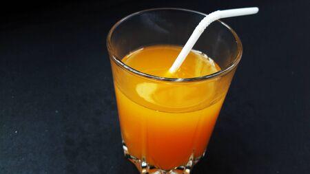 orange juice glass isolated on black background