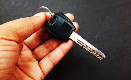 car key in hand isolated on black background Standard-Bild