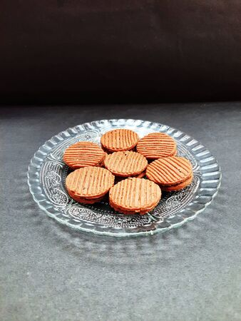 chocolate cookies on plate isolated on black background