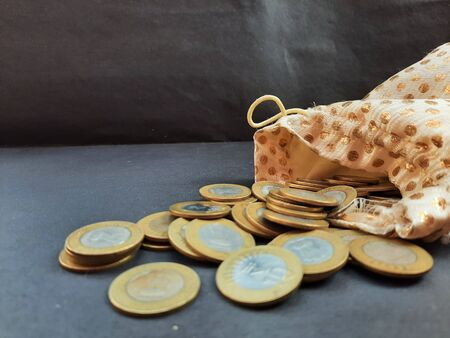 indian coins with golden pouch isolated on black background 写真素材