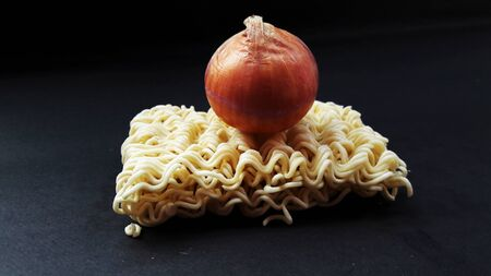 raw noodle onion on it isolated on black background Imagens