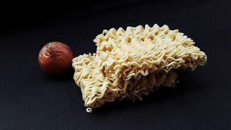 raw noodle with onion isolated on black background