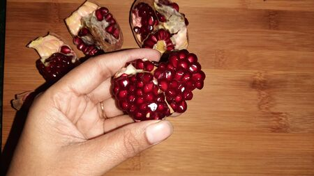 pomegranate and its seeds on wooden background with text space
