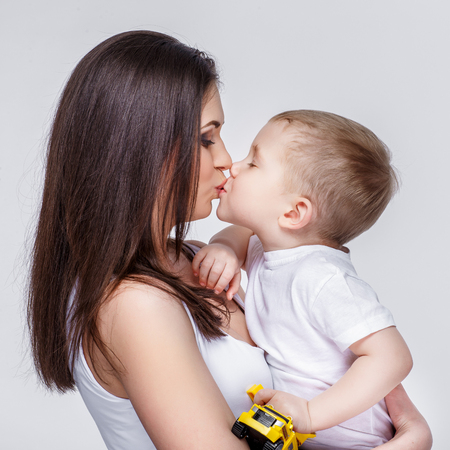 niños riendose: happy young mother with a child on light grey background
