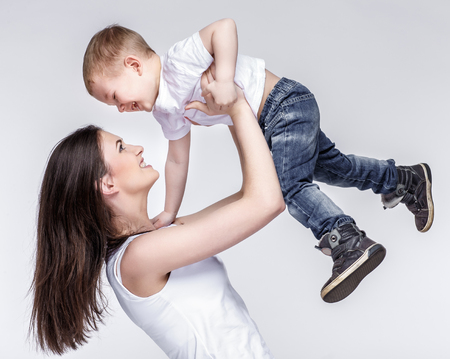 happy young mother with a child on light grey background