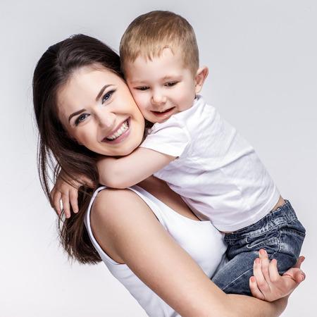 enfant qui joue: jeune mère heureuse avec un enfant sur fond gris clair