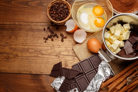 Baking chocolate cake in rural or rustic kitchen. Dough recipe ingredients on vintage wooden table