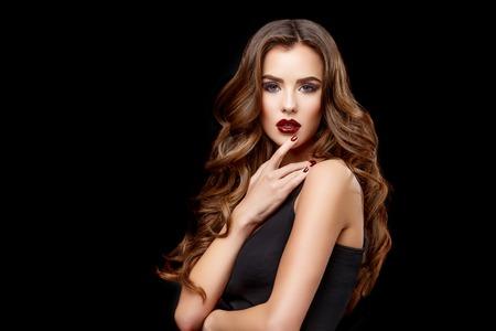 청소 신선한 피부와 건강한 곱슬 머리를 가진 젊은 여자의 아름다운 얼굴은 검은 배경에 닫습니다