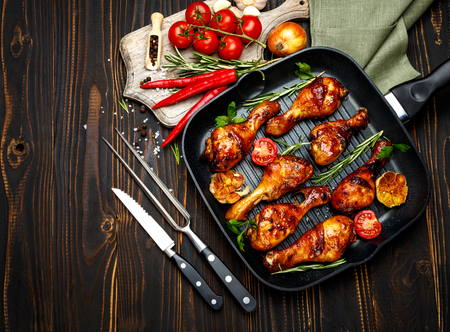 roasted chicken legs with herbs on wooden table