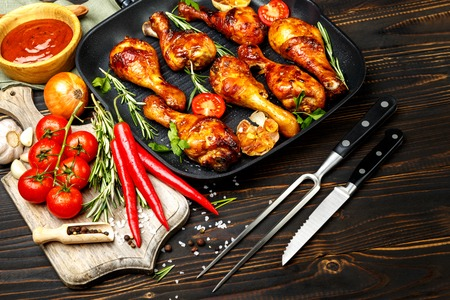 roasting pan: roasted chicken legs with herbs on wooden table