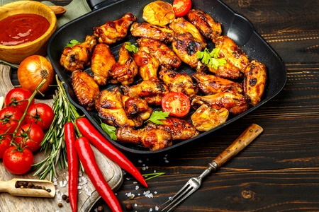 roasting pan: roasted chicken wings with herbs on wooden table