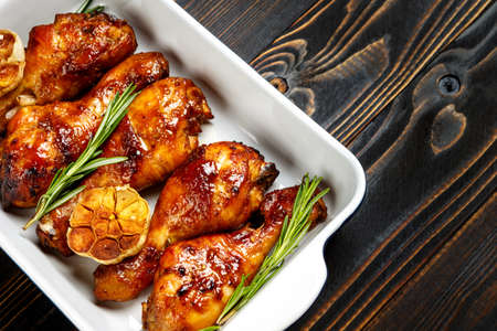 drumsticks: roasted chicken legs with herbs on wooden table