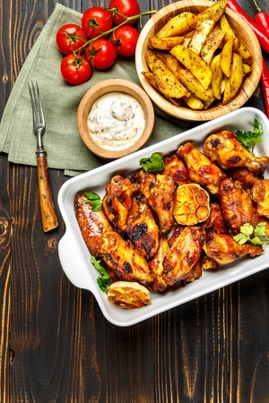 roasted chicken wings with herbs on wooden table