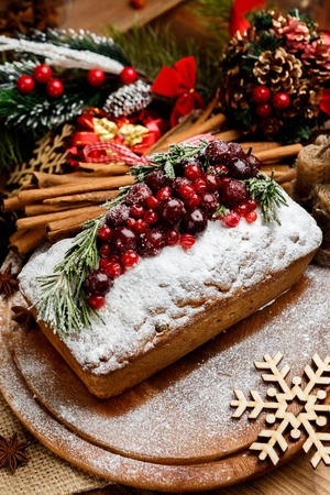 fruit plate: Homemade christmas cake with wild berries on woonen background