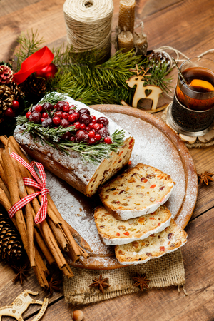 Homemade christmas cake with wild berries on woonen background
