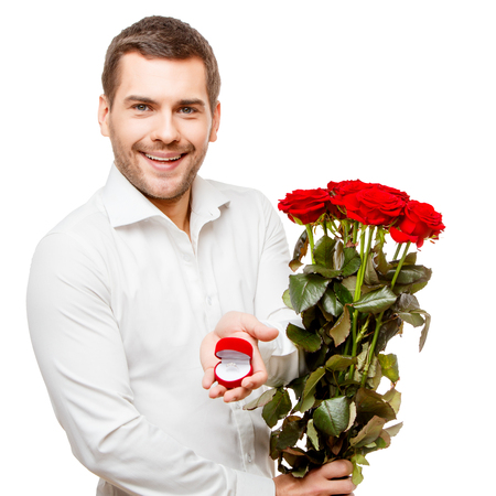 heart shaped box: Young man carries heart shaped box and flowers, isolated on white Stock Photo
